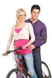 Un par joven en el amor que presenta en una bici Foto de archivo