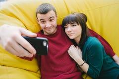Un par joven en la diversión del inconformista del amor que hace el selfie en su smartphone Retrato de la gente joven en el cuart Imagen de archivo
