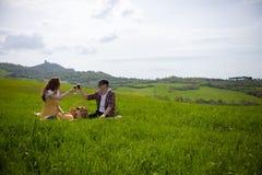 Un par joven en la ropa brillante que se sienta en un prado verde claro y un vino de consumici?n aclamaciones imágenes de archivo libres de regalías