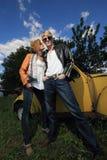 Un par joven en un coche viejo en un campo Fotos de archivo