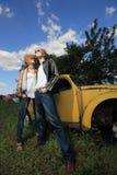 Un par joven en un coche viejo en un campo Imagen de archivo libre de regalías
