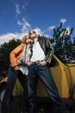 Un par joven en un coche viejo en un campo Imágenes de archivo libres de regalías
