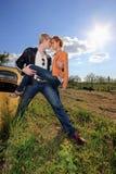 Un par joven en un coche viejo en un campo Foto de archivo libre de regalías
