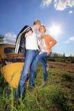 Un par joven en un coche viejo en un campo Fotografía de archivo libre de regalías