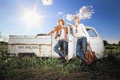 Un par joven en un coche viejo en un campo Foto de archivo