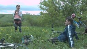 Un par joven en un viaje de la bici arregló un alto Una muchacha hermosa está bebiendo té después de que sea un paseo de la bici, almacen de video