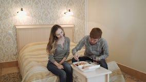 Un par joven en una habitación de lujo come el sushi de una caja del almuerzo y bebe el vino rojo almacen de metraje de vídeo