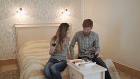 Un par joven en una habitación de lujo come el sushi de una caja del almuerzo y bebe el vino rojo metrajes