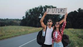 Un par joven está haciendo autostop la situación en el camino Un hombre y una mujer parar el coche en la carretera con un futuro  metrajes