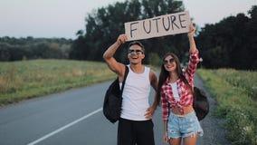 Un par joven está haciendo autostop la situación en el camino Un hombre y una mujer parar el coche en la carretera con un futuro  almacen de metraje de vídeo
