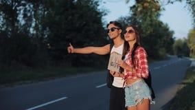 Un par joven está haciendo autostop la situación en el camino Un hombre y una mujer parar el coche en la carretera con una muestr almacen de metraje de vídeo
