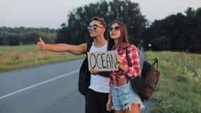Un par joven está haciendo autostop la situación en el camino Un hombre y una mujer parar el coche en la carretera con un océano  metrajes