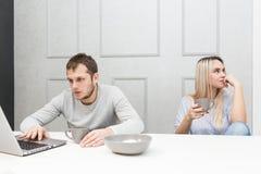 Un par joven está teniendo el hombre del desayuno A trabaja detrás de un ordenador portátil, una mujer aburrida mira al lado fotos de archivo