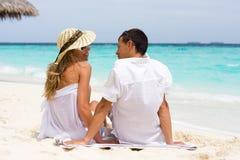 Un par joven feliz en una playa Foto de archivo libre de regalías