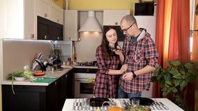 Un par joven fija la tabla, preparándose para la cena Placas, jugo, comida El hablar en el teléfono en la cocina metrajes