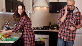 Un par joven fija la tabla, preparándose para la cena Placas, jugo, comida El hablar en el teléfono en la cocina almacen de video