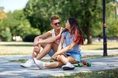 Un par joven hermoso del caída-en-amor que se sienta en la tierra en un fondo borroso del parque Relación y concepto del amor Foto de archivo libre de regalías