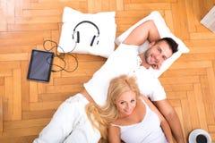 Un par joven hermoso en el piso en su nuevo hogar Foto de archivo libre de regalías