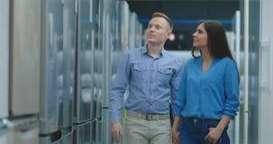 Un par joven, un hombre y una mujer elegir un nuevo refrigerador Abren la puerta y la mirada en el espacio y la conveniencia almacen de video
