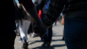 Un par joven que camina llevando a cabo las manos alrededor de una muchedumbre almacen de video