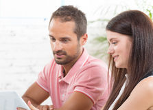 Un par joven que mira una tableta Fotografía de archivo