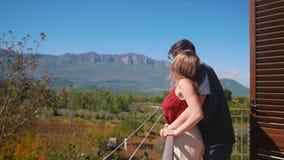 Un par joven que sale en el balcón, abrazo y disfrutando de la visión almacen de metraje de vídeo