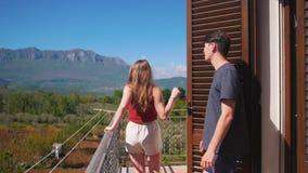Un par joven que sale en el balcón y el abrazo almacen de metraje de vídeo