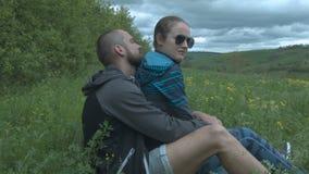 Un par joven se está sentando en el campo Un hombre y una mujer hermosos se están sentando en los brazos en la naturaleza almacen de metraje de vídeo