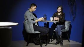 Un par joven se sienta en un café y utiliza los teléfonos Un hombre y una mujer que practican surf Internet en smartphones Depend almacen de video