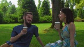 Un par joven se sienta en la tierra en el café del parque y de la bebida almacen de video