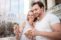 Un par joven usando el teléfono elegante Fotos de archivo