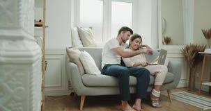 Un par lindo en pijamas tiene una época junta en la mañana que se sienta en el sofá y que mira a través del cuaderno almacen de metraje de vídeo