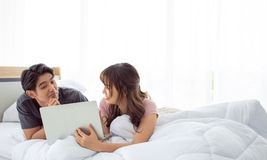 Un par lindo está utilizando el ordenador portátil junto en el dormitorio imágenes de archivo libres de regalías