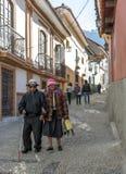 Un par mayor camina abajo de una calle en la vieja sección de la ciudad de La Paz en Bolivia Foto de archivo