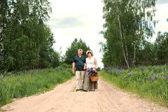 Un par mayor camina a través del bosque y un hombre da a mujer una cesta tejida con un ramo de flores de lupines púrpuras fotografía de archivo