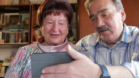 Un par mayor comunica con su nieto por el vídeo que liga la tableta Un hombre y una mujer están hablando con almacen de metraje de vídeo