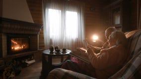 Un par mayor considera a una familia que el álbum de foto envolvió en una manta que se sentaba por una chimenea acogedora almacen de metraje de vídeo
