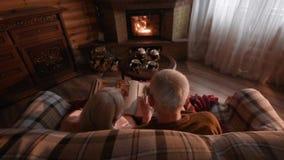 Un par mayor está considerando a una familia que el álbum de foto envolvió para arriba en una tela escocesa metrajes