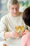 Un par mayor feliz que tuesta sus años junto con champag Imagen de archivo