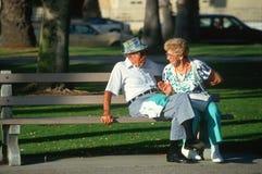 Un par mayor que se sienta en un banco de parque Fotos de archivo