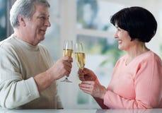 Un par mayor que tuesta sus años junto con champag Foto de archivo