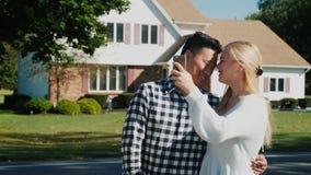 Un par multinacional joven se fotografía contra el contexto de su nuevo hogar Concepto - estreno de una casa, a de compra almacen de video