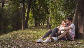 Un par precioso que abraza en un parque por la mañana foto de archivo