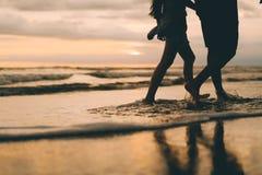 Un par que camina cerca de la puesta del sol de observación del océano imagen de archivo libre de regalías