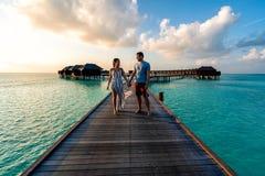 Un par que disfruta de una salida del sol en los Maldivas fotos de archivo