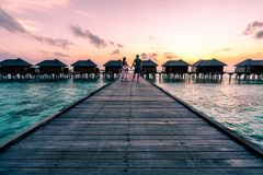Un par que disfruta de una salida del sol en los Maldivas foto de archivo
