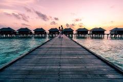 Un par que disfruta de una salida del sol en los Maldivas fotografía de archivo libre de regalías