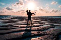Un par que disfruta de una salida del sol en los Maldivas imagen de archivo
