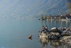 Un par que juega con el perro en el lago Brienz fotos de archivo