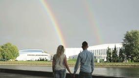Un par que lleva a cabo las manos y que mira dos arco iris almacen de metraje de vídeo